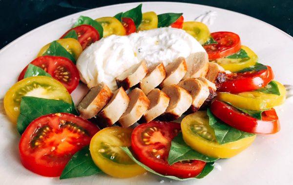 Bratwurst neben frischen Tomaten